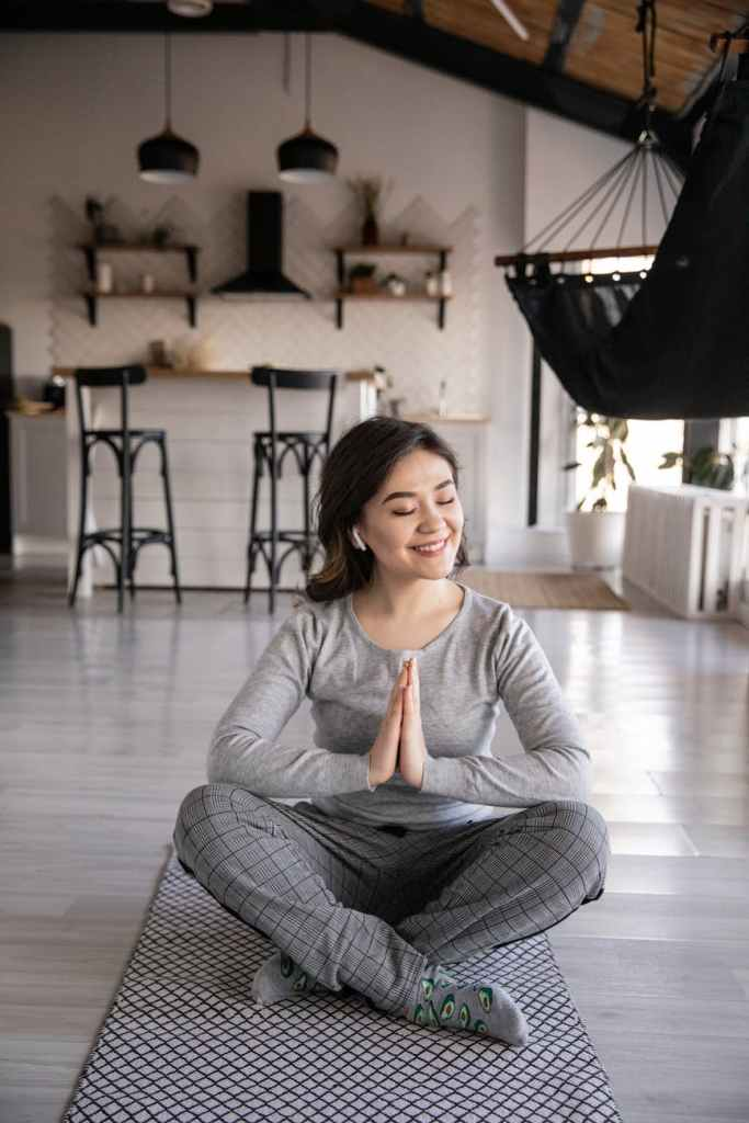 A 30-something woman, in work clothes, is seated on a mat on the floor meditating. A smile is on her face.